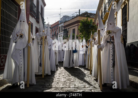 Nazarenos participating in a religious procession, with the traditional robes and hoods and carrying candles during - Stock Photo