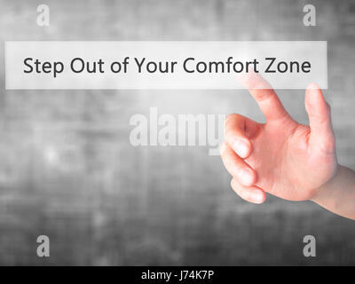 Step Out of Your Comfort Zone - Hand pressing a button on blurred background concept . Business, technology, internet concept. Stock Photo