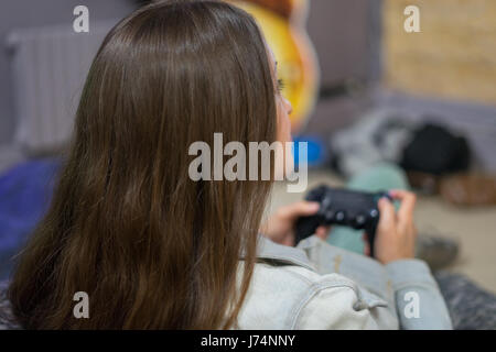 gamer girl playing video games with joystick sitting on Bean bag chair - Stock Photo