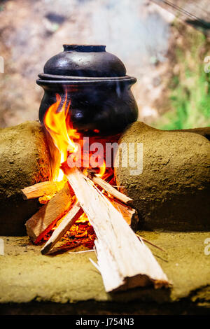 A clay pot cooking and heated over a wood fired stove made out of mud and clay in a traditional outdoor Sri Lankan - Stock Photo