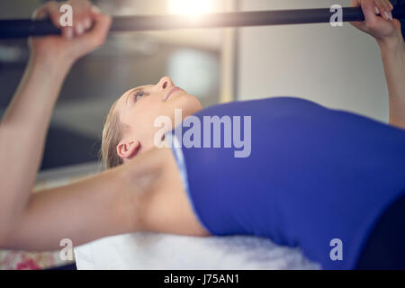 Close-up side view of young blonde woman in blue top doing bench pressing exercise with bar-bell in gym - Stock Photo