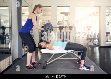 Young woman working out with barbell weights on a bench in the gym with the assistance of her personal trainer in - Stock Photo