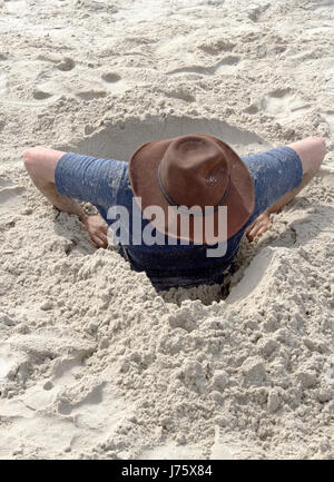 A young man attempts to dig himself out of a hole in the sand that he's gotten himself into on a beach one sunny - Stock Photo