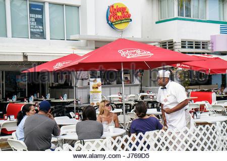 Miami Beach Florida Ocean Drive Art Deco District restaurant alfresco dining tables Johnny Rockets Black man waiter - Stock Photo