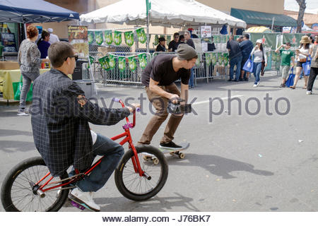 Miami Florida Little Havana Calle Ocho Street Festival Hispanic teen boy male bicycle skateboard video camera - Stock Photo