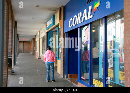 Coral Betting shop and Greggs Bakery next to each other on the high street in Market Drayton, Shropshire - Stock Photo
