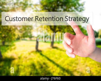 Customer Retention Strategy - Hand pressing a button on blurred background concept . Business, technology, internet - Stock Photo