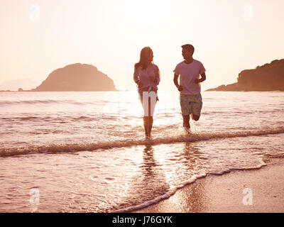 happy young asian couple running on beach in early morning. - Stock Photo
