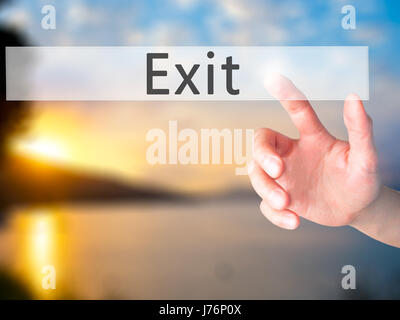 Exit - Hand pressing a button on blurred background concept . Business, technology, internet concept. Stock Photo - Stock Photo