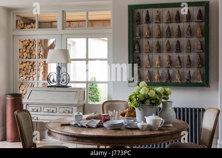 Penguin firgurines displayed in a bold green frame on wall of kitchen. The bureau, the lamp and the circular table - Stock Photo
