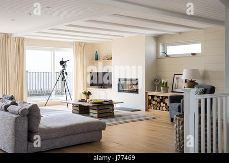 Light filled sitting room with balcony and telescope. The coffee table is made from old apple crates and the modular - Stock Photo