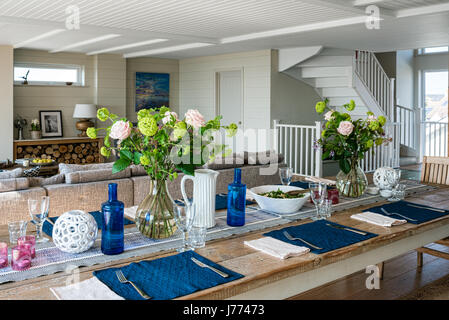 Lunch laid on wooden farm house table in open plan kitchen diner - Stock Photo