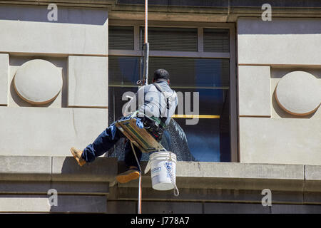 man cleaning windows using abseil rope techniques Washington DC USA - Stock Photo