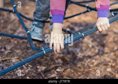 Cropped image of boy playing on jungle gym - Stock Photo