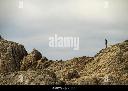 Mid distance view of man walking on mountain against sky - Stock Photo