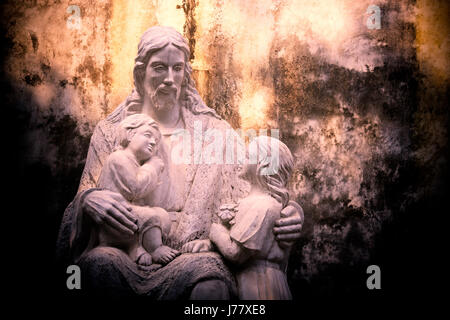 Statue of Jesus holding two infants in his arms, St Josephs Cathedral, Hanoi, Vietnam - Stock Photo