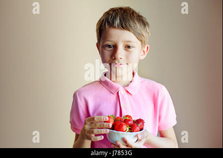 Cute little boy holding bowl with strawberries - Stock Photo
