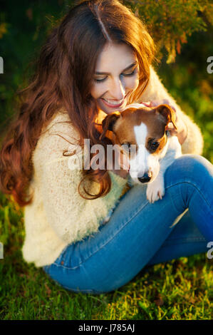 Girl with a dog Jack Russell Terrier in park - Stock Photo