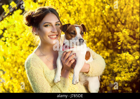 Beautiful woman playing with her dog. Outdoor portrait. series - Stock Photo