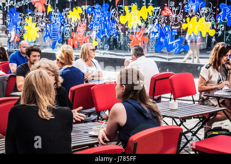 People sitting at an outdoor cafe in Covent Garden with the mirrors of Reflect London behind. - Stock Photo