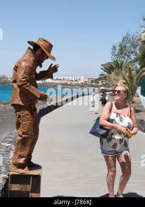 A tourist passing a street entertainer, Avenida los Cocederos, Costa Teguise, Lanzarote, Canary Islands Europe - Stock Photo
