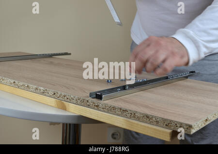 Man working - installing rails with a screwdriver on an element of a cabinet in his apartment - Stock Photo