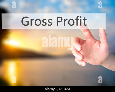 Gross Profit - Hand pressing a button on blurred background concept . Business, technology, internet concept. Stock - Stock Photo