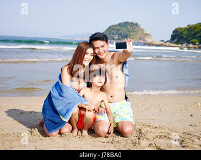 asian mother father and son taking a selfie on beach. - Stock Photo