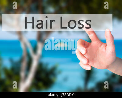 Hair Loss - Hand pressing a button on blurred background concept . Business, technology, internet concept. Stock - Stock Photo