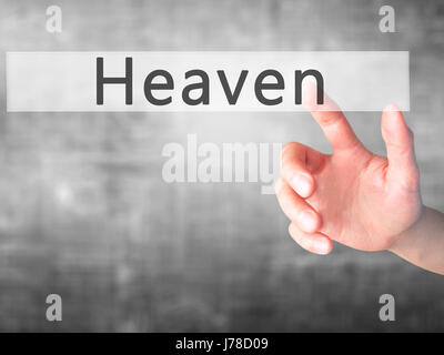 Heaven - Hand pressing a button on blurred background concept . Business, technology, internet concept. Stock Photo - Stock Photo