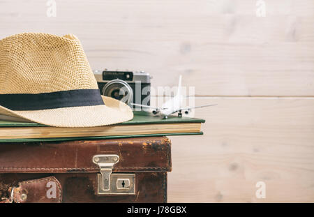 Travel accessories on an old suitcase - white wooden background - copy space