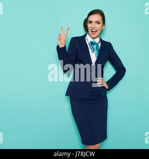 Happy stewardess in blue formal wear is showing peace hand sign, shouting and looking at camera. Three quarter length - Stock Photo