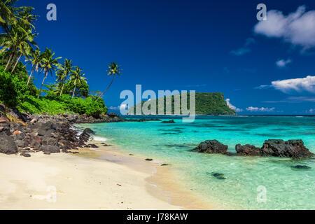 Vibrant tropical Lalomanu beach on Samoa Island with coconut palm trees and black rocks - Stock Photo