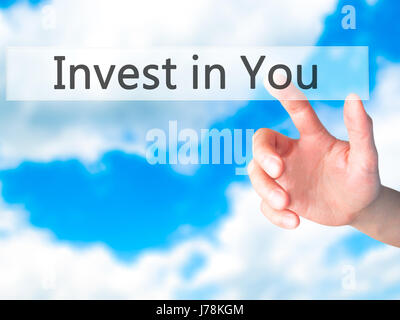 Invest in You - Hand pressing a button on blurred background concept . Business, technology, internet concept. Stock - Stock Photo
