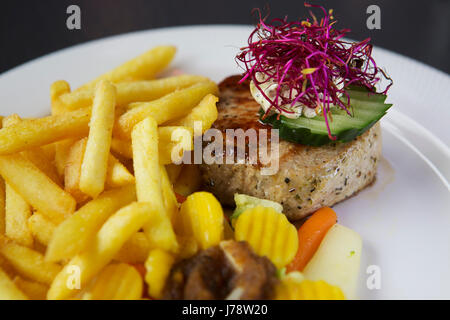 Pork steak served with French fries and vegetables at Interlaken in Switzerland. Butter is topped with purple flowers. - Stock Photo