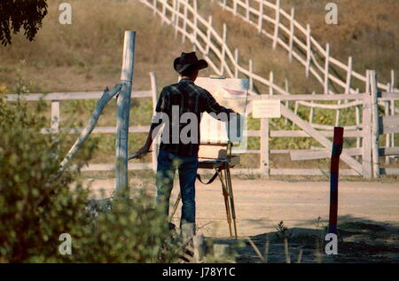 Artist in cowboy hat paints a picture of oil painting. Outside, near the ranch farm. - Stock Photo