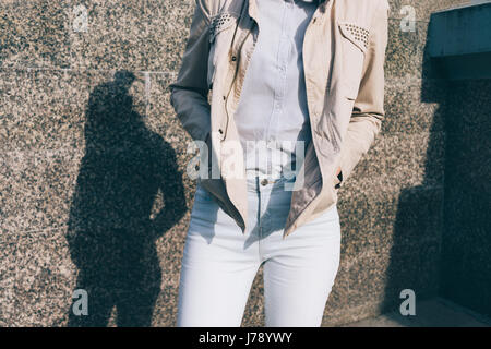 Woman in jeans, shirt and a beige jacket in the background of the marble wall. Details of women's clothing, close - Stock Photo