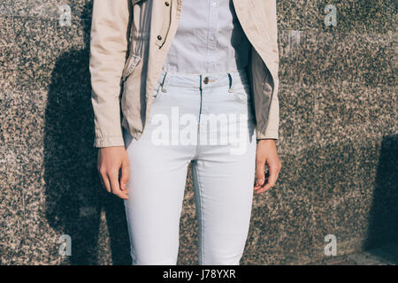 Details of women's clothing: a girl in jeans, shirt and a beige jacket on a background of a marble wall - Stock Photo