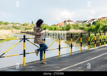 Young beautiful woman hipster standing next to the lake and texting messages on a mobile phone - Stock Photo