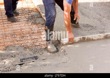 Workers work on concreting parking spaces in front of the house. Mason worker leveling concrete with trowels mason - Stock Photo