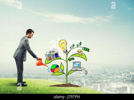 Young businessman outdoors watering drawn growth concept with can - Stock Photo