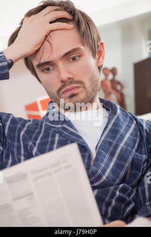 newspaper journal gesturing bathrobe expression emotion man home newspaper - Stock Photo