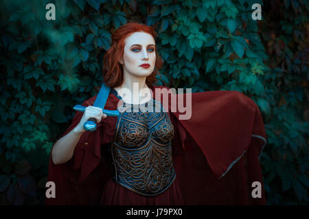 Red-haired girl warrior. In hands holds a sword on the chest wearing cuirass. Stock Photo