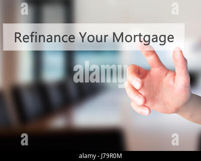 Refinance Your Mortgage - Hand pressing a button on blurred background concept . Business, technology, internet - Stock Photo