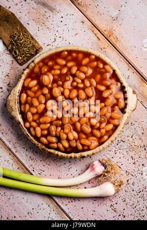 high-angle shot of an earthenware bowl full of baked beans and some green garlics on a rustic wooden table - Stock Photo