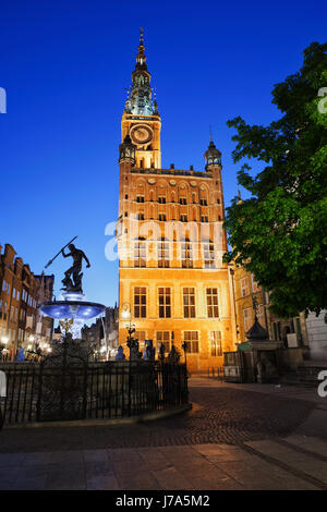 Poland, Gdansk, view to lighted town hall with Neptune Fountain in the foreground at night - Stock Photo