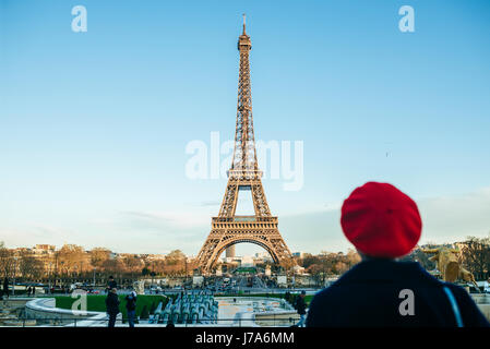 France, Paris, view to Eiffel Tower with back view of young woman standing in the foreground - Stock Photo