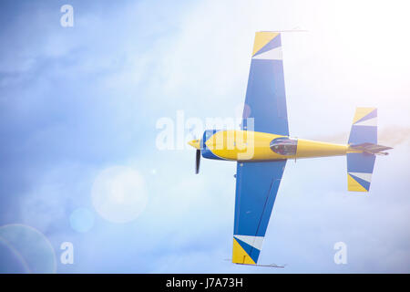 A small sport plane flying in the sky. A sun flare in the corner. Color of the plane is bluуand yellow. a pilot - Stock Photo