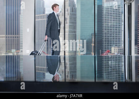 Businessman walking with rolling suitcase in city office - Stock Photo