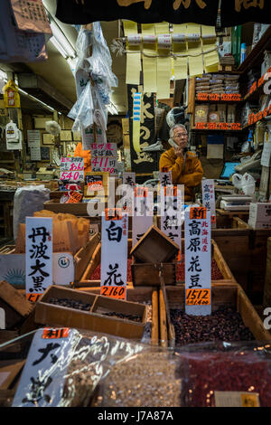 A shopkeeper in a bean shop in the Tsukiji outer market is on the phone. The shop is small and cramped but vibrant - Stock Photo